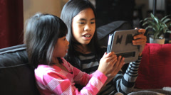 Asian Sisters Playing Games On Tablet Together Stock Footage