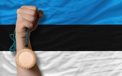 bronze medal for sport and  national flag of estonia - stock photo
