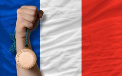 Stock Photo of bronze medal for sport and  national flag of france