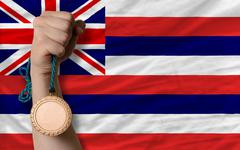 bronze medal for sport and  flag of american state of hawaii - stock photo