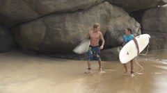 Surfers walking out of the water talking about waves Stock Footage