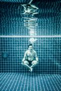 Man under water in a swimming pool to relax in the lotus position Stock Photos