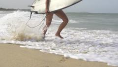 SLOW MOTION: Young female surfer running in shallow water Stock Footage