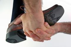 Hands boosting a shoe Stock Photos