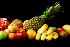 Assorted fresh fruit arranged in line - stock photo