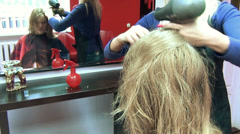 Hairdresser barber blow dry customer woman hair in barber salon Stock Footage