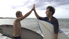 SLOW MOTION: Surfers high five Stock Footage