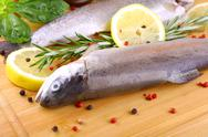 Stock Photo of two fresh rainbow trout, spices and lemon on bamboo board