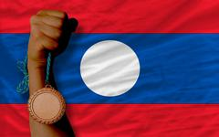 bronze medal for sport and  national flag of laos - stock photo