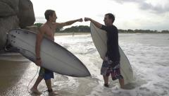 SLOW  MOTION: Surfers fist bump Stock Footage