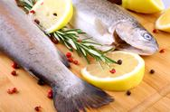 Stock Photo of two fresh rainbow trout with spices, red pepper and lemon