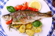 Stock Photo of grilled rainbow trout with potato, basil, red pepper and lemon