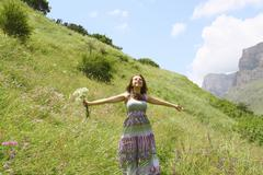 young girl enjoying the outdoors on a meadow in the mountains - stock photo