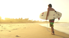 Surfer walking out of the water after session at sunset Stock Footage