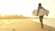Stock Video Footage of Surfer walking out of the water after session at sunset