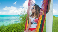 Young Woman on Colorful Hammock in Bermuda Overlooking Tropical Ocean - stock footage