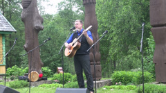 Bard performs creative song playing guitar country park Stock Footage