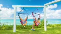 Girl in Bermuda Sitting on Colorful Hammock Overlooking Tropical Ocean Stock Footage