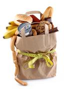 Paper shopping bag with high-calorie foods and measuring tape Stock Photos