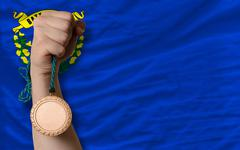 bronze medal for sport and  flag of american state of nevada - stock photo