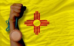 bronze medal for sport and  flag of american state of new mexico - stock photo