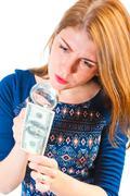 Girl carefully considering the money through a magnifier Stock Photos