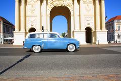 Stock Photo of brandenburg gate in potsdam and retro car
