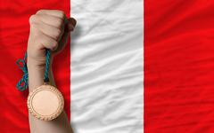 Stock Photo of bronze medal for sport and  national flag of peru