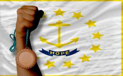 bronze medal for sport and  flag of american state of rhode island - stock photo