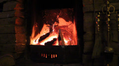 Close up Of Open Old Wood Fireplace Lit With Flames With Brushes Stock Footage