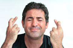 Mature man with crossed fingers hoping for good luck Stock Photos