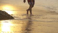 SLOW MOTION: Man walking in surf at sunset Stock Footage