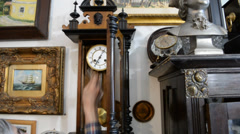 In an antique shop. Seller and antique clock Stock Footage