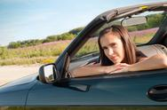 Stock Photo of Beautiful brunette female sitting in car