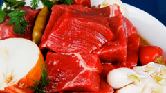 Meat chunks on white bowls with vegetables and red peppers Stock Footage