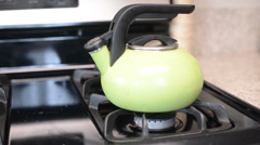Turning on gas stove with tea kettle - stock footage