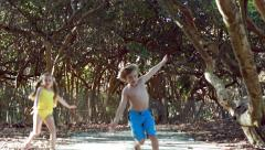Kids In Swimsuits Pretend To Fly Down Path Stock Footage