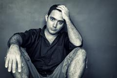 desaturated  image of a stressed and worried young man - stock photo