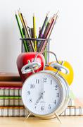 Back to school , note book , clock , pencil , apple on wood table Stock Photos