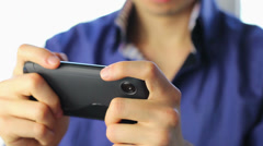 Man playing sensor games on touch phone, YES, losing, close-up - stock footage