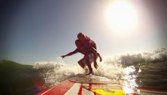 Father and 4 year old daughter surf together Stock Footage