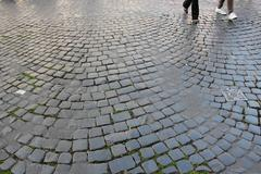 Young feet on an old roman cobblestone road Stock Photos