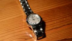 A Silver Metal Watch Ticks Away on a Wooden Desk Stock Footage