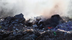 Pollution from burning trash at garbage dump with smoke from an open fire Stock Footage
