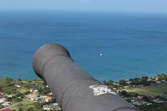 Old cannon overlooking the azure waters of the caribbean sea Stock Photos
