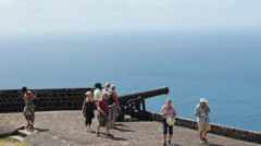 Tourists explore cannon on old fort on caribbean island Stock Footage