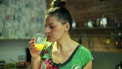 Woman eating and drinking juice in the kitchen Stock Footage