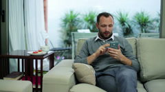 Man with a cellphone sitting on the sofa Stock Footage