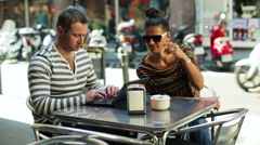waitress bringing coffee for a couple sitting by the table - stock footage