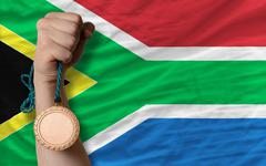 Stock Photo of bronze medal for sport and  national flag of south africa